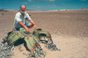 Bruce in the Namib Desert, Africa, next to rare and ancient Welwitschia mirabilis plant